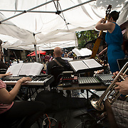 """June 21, 2014 - New York, NY : <br /> The city was flooded with music on Saturday as Make Music New York brought more than 1,300 free concerts to the city's streets and parks. The annual festival's program included the performance """"'In (Key)' - New Compositions in Celebration of Terry Riley's 'In C' @ 50 Years"""" on Cornelia Street, in front of the Cornelia Street Cafe in Greenwich Village, on Saturday afternoon. Pictured here, the musicians including Eleanor Sandresky, foreground left on keyboard, and Adam Cuthbért, foreground right on trumpet and software instruments, perform under a tent in the middle of Cornelia Street on Saturday afternoon.<br /> CREDIT: Karsten Moran for The New York Times"""