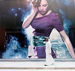 Arab man walking in front of fashion billboard in shopping mall in Dubai United Arab Emirates UAE