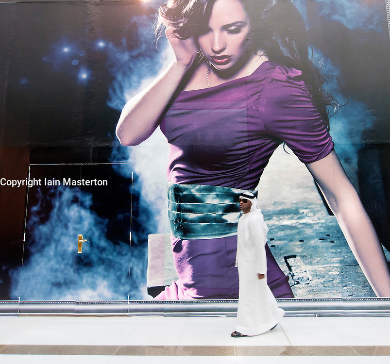 Arab man walking in front of fashion billboard in shopping mall in Dubai United Arab Emirates UAE