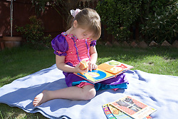 Little girl reading a book in the garden,