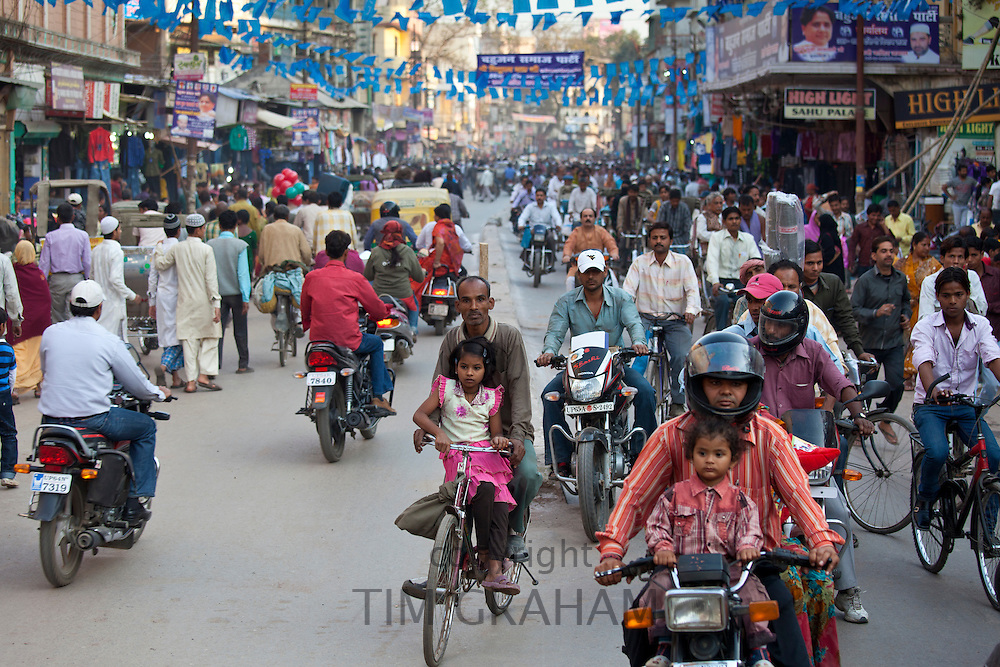 Fathers with children on cycles in crowded street scene during holy Festival of Shivaratri in city of Varanasi, Benares, Northern India RESERVED USE - NOT FOR DOWNLOAD -  FOR USE CONTACT TIM GRAHAM