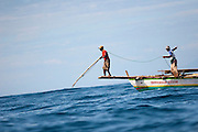 A Lamafa prepare to  spear a sperm whale from his boat. Residents in the lamalera village, Indonesia cathing  sperm whales with traditional method to provide meals for the entire village and part of the Lembata island where the village is located..