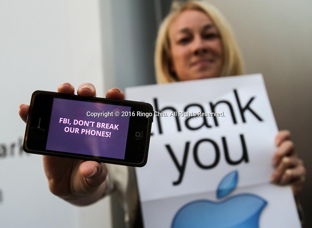 2月23日,示威者在洛杉矶一家苹果专卖店外示威。当天,示威活动在美国、甚至美国以外超过30多个城市的多家苹果零售店展开,声援苹果公司拒绝帮助美国执法部门解除一部在去年12月2日美国加州南部圣贝纳迪诺恐怖袭击案中枪手的智能手机开机密码。新华社发 (赵汉荣摄)<br /> A demonstrator shows her iPhone outside the Apple store, Tuesday, Feb. 23, 2016, in Los Angeles, the United States. Protesters assembled in more than 30 cities around the world to lash out at the FBI for obtaining a court order that requires Apple to make it easier to unlock an encrypted iPhone used by a gunman in December's mass murders in California. (Xinhua/Zhao Hanrong)(Photo by Ringo Chiu/PHOTOFORMULA.com)<br /> <br /> Usage Notes: This content is intended for editorial use only. For other uses, additional clearances may be required.