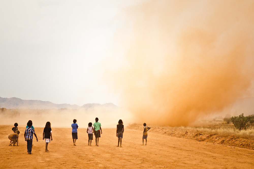 Children on the track watch cautiously as a WilliWilli or Dust Devil Spins past at Santa Teresa Races.