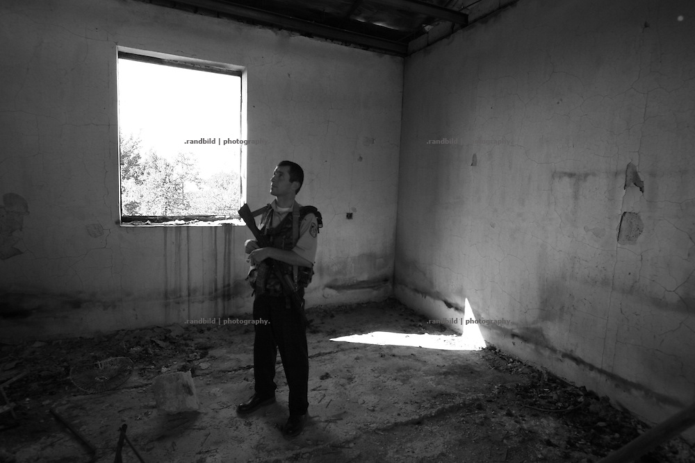 An armed georgian policeman patrols in a burnt out house in Ergneti, located in the so called bufferzone between Gori and Tskhinvali, a few days after the withdrawal of the russian forces. The bufferzone was etablished after a short war in August 2008 as the georgian army assulted South Ossetia to overthrow the local separatist government.