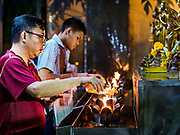 31 DECEMBER 2018 - BANGKOK, THAILAND: A man makes merit by pouring oil into oil lamps during New Year's Eve prayers and meditation at Wat Pathum Wanaram in central Bangkok. Many Thais go to temples to meditate and pray on New Year's Eve.    PHOTO BY JACK KURTZ
