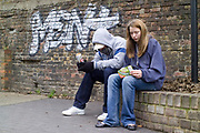Two teenagers hanging out on the street, drinking alcohol and smoking, UK 2008