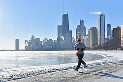 © Licensed to London News Pictures. 27/12/2017. CHICAGO, USA.  A man is seen out for a run near North Avenue Beach.  The city of Chicago experiences sub-zero temperatures.  With the effects of wind chill, temperatures are expected to be -22C to -32C.  Photo credit: Stephen Chung/LNP