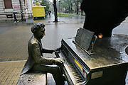 Lodz, Poland main street. (Piotrkowska St.) Bronze statue of Arthur Rubenstein playing his piano.