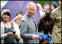 HRH The Prince Of Wales holds Zephyr the Eagle while visiting the Sandringham Flower Show<br /> Sandringham, Norfolk, United Kingdom<br /> Wednesday, 31st July 2013<br /> Picture by Andrew Parsons / i-Images