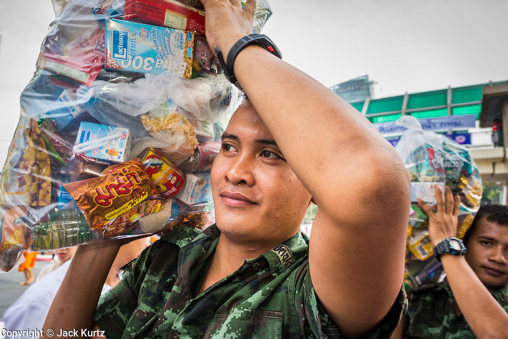 08 SEPTEMBER 2013 - BANGKOK, THAILAND: Thai soldiers carry donated food and supplies to a waiting truck after a mass alms giving ceremony in Bangkok Sunday. 10,000 Buddhist monks participated in a mass alms giving ceremony on Rajadamri Road in front of Central World shopping mall in Bangkok. The alms giving was to benefit disaster victims in Thailand and assist Buddhist temples in the insurgency wracked southern provinces of Thailand.      PHOTO BY JACK KURTZ