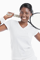Portrait of young female tennis player holding racket over white background
