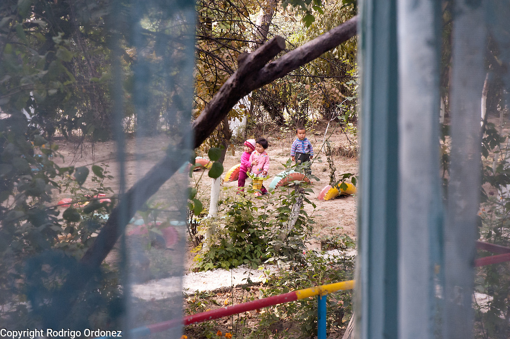 Children can be seen through a window at the playground of Kindergarten 29, in Osh (Kyrgyzstan), where Save the Children supports a child-friendly space.