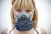 Chinese artist Li Shurui in the mask she wears when airbrushing in her studio in Beijing.