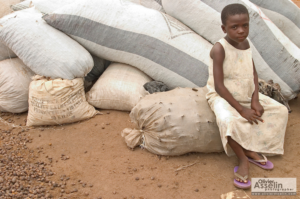 Young girl sitting on palm nut bags at palm oil processing plant outside Ashaiman, one of Ghana's largest slums. The plant is set a few meters away from a large garbage dump.
