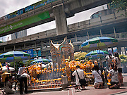 "11 JULY 2011 - BANGKOK, THAILAND:   The BTS ""Skytrain"" runs past the Erawan Shrine in Bangkok. The Erawan Shrine (in Thai San Phra Phrom) is a Hindu shrine in Bangkok, Thailand that houses a statue of Phra Phrom, the Thai representation of the Hindu creation god Brahma. A popular tourist attraction, it often features performances by resident Thai dance troupes, who are hired by worshippers in return for seeing their prayers at the shrine answered. On 21 March 2006, a man vandalised the shrine and was subsequently killed by bystanders. The shrine is located by the Grand Hyatt Erawan Hotel, at the Ratchaprasong intersection of Ratchadamri Road in Pathum Wan district, Bangkok, Thailand. It is near the Bangkok Skytrain's Chitlom Station, which has an elevated walkway overlooking the shrine. The area has many shopping malls nearby, including Gaysorn, CentralWorld and Amarin Plaza. The Erawan Shrine was built in 1956 as part of the government-owned Erawan Hotel to eliminate the bad karma believed caused by laying the foundations on the wrong date..The hotel's construction was delayed by a series of mishaps, including cost overruns, injuries to laborers, and the loss of a shipload of Italian marble intended for the building. Furthermore, the Ratchaprasong Intersection had once been used to put criminals on public display. An astrologer advised building the shrine to counter the negative influences. The Brahma statue was designed and built by the Department of Fine Arts and enshrined on 9 November 1956. The hotel's construction thereafter proceeded without further incident. In 1987, the hotel was demolished and the site used for the Grand Hyatt Erawan Hotel.     PHOTO BY JACK KURTZ"