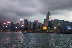 Hong Kong, China skyline lit up against a stormy evening sky viewed across Victoria Harbor.