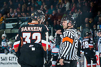 KELOWNA, CANADA - FEBRUARY 28: Travis Sanheim #32 of Calgary Hitmen discusses a call with referee Chris Crich at the Kelowna Rockets on February 28, 2015 at Prospera Place in Kelowna, British Columbia, Canada.  (Photo by Marissa Baecker/Shoot the Breeze)  *** Local Caption *** Travis Sanheim; Chris Crich;