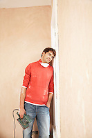 Man  holding sanding tool leaning against wall of unrenovated room