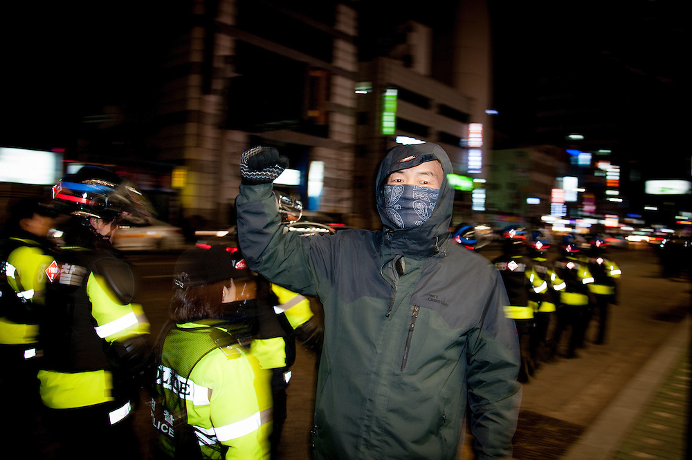 A man protests in front of police at a labor rally in support of workers from KORAIL, the state rail service, Busan, South Korea.