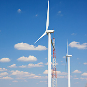 Wind Turbine Farm The Jersey-Atlantic Wind Farm (located in Atlantic City, NJ, USA) is a joint project by Community Energy Inc. (CEI), a subsidiary of Iberdrola, and the Atlantic County Utilities Authority (ACUA). The wind generation facility is sized to meet the electrical load requirements of the ACUA Wastewater Treatment Facility with remaining excess energy being sold to the regional power grid. The wind farm consists of five 1.5-megawatt wind turbines manufactured by General Electric. The towers are approximately 262 feet high with three rotors of 118 feet for a total height of about 380 feet.