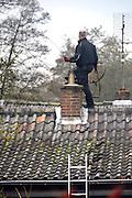 Nederland, Ubbergen, 23-11-2016Een schoorsteenveger, veegt het rookkanaal van een houtkachel. Het is een officiele, gecertificeerde schoorsteenveegbedrijfFoto: Flip Franssen