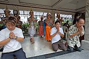 Erawan shrine. Thai dance dedicated by the spenders kneeling in front.