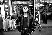 Shanghai Portraits 1 - A young man in a faux leather jacket and matching pants poses on the street in central Shanghai. .Shanghai's old neighborhoods are quickly being demolished and replaced with modern skyscrapers. The alleys and small lanes that make up the heart of China's largest city are still bustling with local flair, but these neighborhoods will soon be reduced to memories...