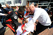 AFC Bournemouth forward Max Gradel signing his autograph on a flag for a fan on arrival for the Premier League match between Bournemouth and Burnley at the Vitality Stadium, Bournemouth, England on 13 May 2017. Photo by Graham Hunt.