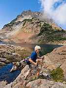 Active senior woman hiker. Del Campo Peak rises above Foggy Lake in Gothic Basin, in the Cascade Mountains of Washington, USA. Hike 10 miles round trip with 3300 feet gain along a mostly steep and rough trail, starting from the trailhead at Barlow Pass on the Mountain Loop Highway, 20 miles east of Verlot Visitor Center, in Mount Baker - Snoqualmie National Forest.