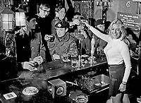 Julie Goodyear better known as Bet Lynch, landlady of Coronation Street's Rover's Return, serving drinks to British soldiers serving in N Ireland after  opening a traditional English pub at Ballykinlar Army Camp, N Ireland.  197212160826c, 825/72.<br /> <br /> Copyright Image from Victor Patterson, 54 Dorchester Park, Belfast, UK, BT9 6RJ<br /> <br /> t1: +44 28 9066 1296 (from Rep of Ireland 048 9066 1296)<br /> t2: +44 28 9002 2446 (from Rep of Ireland 048 9002 2446)<br /> m: +44 7802 353836<br /> <br /> victorpattersonbelfast@gmail.com<br /> victorpatterson@me.com<br /> <br /> www.victorpatterson.com<br /> <br /> Please see my Terms and Conditions of Use at https://www.victorpatterson.com/page2<br /> It is IMPORTANT that you familiarise yourself with them.<br /> <br /> Images used on the Internet incur an additional cost and must be visibly watermarked i.e. © Victor Patterson within the body of the image and copyright metadata must not be deleted. Images used on the Internet have a size restriction of 4kbs and are chargeable at rates available at victorpatterson.com.<br /> <br /> This image is available only for the use of the download recipient i.e. television station, newspaper, magazine, book publisher, etc, and must not be passed on to any third party. It is also downloaded on condition that each and every usage is notified within 7 days to victorpatterson@me.com<br /> <br /> The right of Victor Patterson (or the named photographer) to be identified as the author is asserted in accordance with The Copyright Designs And Patents Act (1988). All moral rights are asserted.