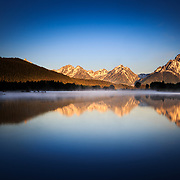 The sunrise reflection of Mount Moran along the still waters of Oxbow Bend in Grand Teton National Park, Wyoming.
