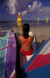 Stock photo of a woman sitting on a surfboard on the beach looking out at windsurfers in Ambergris Caye, Belize.