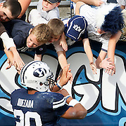 BYU tailback Joshua Quezada celebrates with fans at the conclusion of an NCAA college football game against UNLV at LaVell Edwards Stadium, Saturday, Nov. 6, 2010, in Provo, Utah.  Quezada scored three touchdowns in their 55- 7 win. (AP Photo/Colin E. Braley)