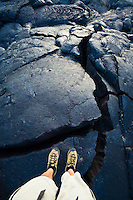 A mans feet and legs standing on a cracked upheaval in a lava flow, Hawai'i Volcanoes National Park