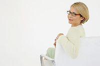 Young blonde woman sits in office chair looking back