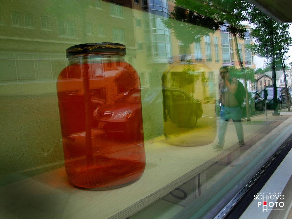 Colored liquid in jars in a window.