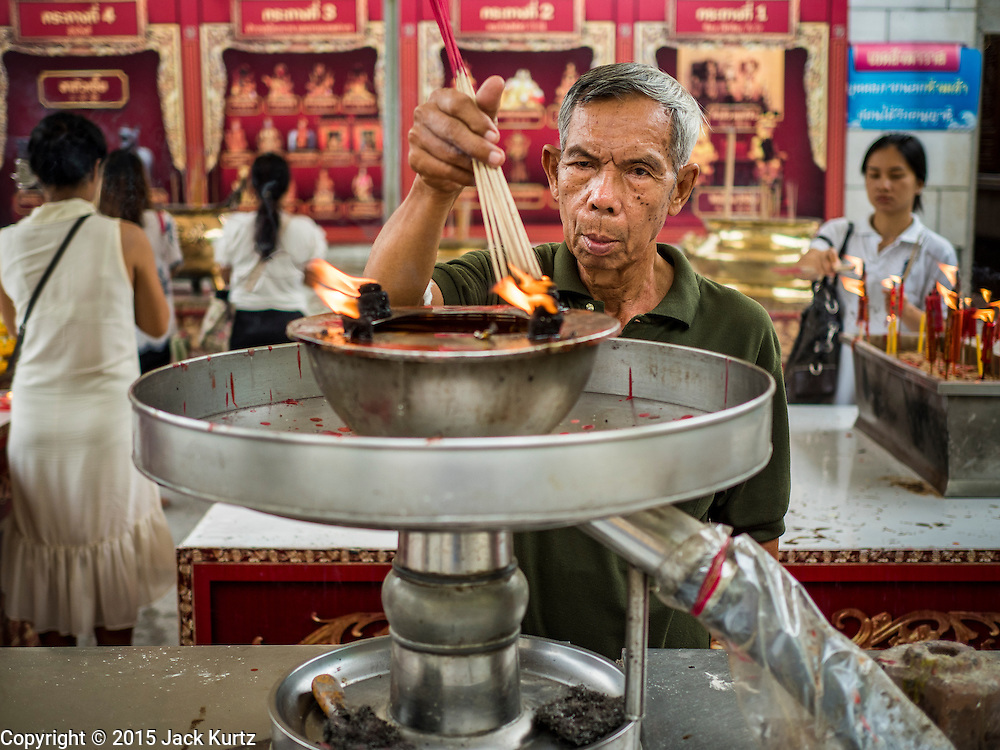 28 AUGUST 2015 - BANGKOK, THAILAND: A man lights incense at Wat Mangkon Kamalawat in the Chinatown section of Bangkok on Hungry Ghost Day. Wat Mangkon Kamalawat is the largest Mahayana Buddhist temple in Chinatown. Mahayana  Buddhists believe that the gates of hell are opened on the full moon of the seventh lunar month of the Chinese calendar, and the spirits of hungry ghosts allowed to roam the earth. These ghosts need food and merit to find their way back to their own. People help by offering food, paper money, candles and flowers, making merit of their own in the process. Hungry Ghost Day is observed in communities with a large ethnic Chinese population, like Bangkok's Chinatown.     PHOTO BY JACK KURTZ