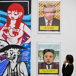 © Licensed to London News Pictures. 12/09/2018. LONDON, UK. A staff member views works depicting Donald Trump and Kim Jung-un by Bart WasNotHere (Myanmar) at the preview of START, a contemporary art fair comprising eclectic works from a variety of international emerging artists.  The fair takes place at the Saatchi Gallery in Chelsea 13 to 16 September 2018.  Photo credit: Stephen Chung/LNP