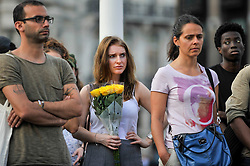 © Licensed to London News Pictures. 19/06/2017. London, UK.  A woman carries a floral tribute as people gather for a vigil in Parliament Square to remember those who died in the Grenfell Tower fire in North Kensington of 14 June.  Mourners and wellwishers were given the opportunity to speak and to write messages on a community banner.  Photo credit : Stephen Chung/LNP