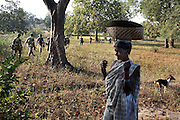 A patrol made up of police and Salwa Judam militia passes a local tribal women in the south Chhattisgarh district of Dantewada.