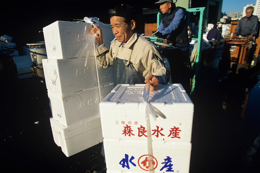 Japan, Tokyo, Worker carrying boxes at crowded Tsukiji Fish Market