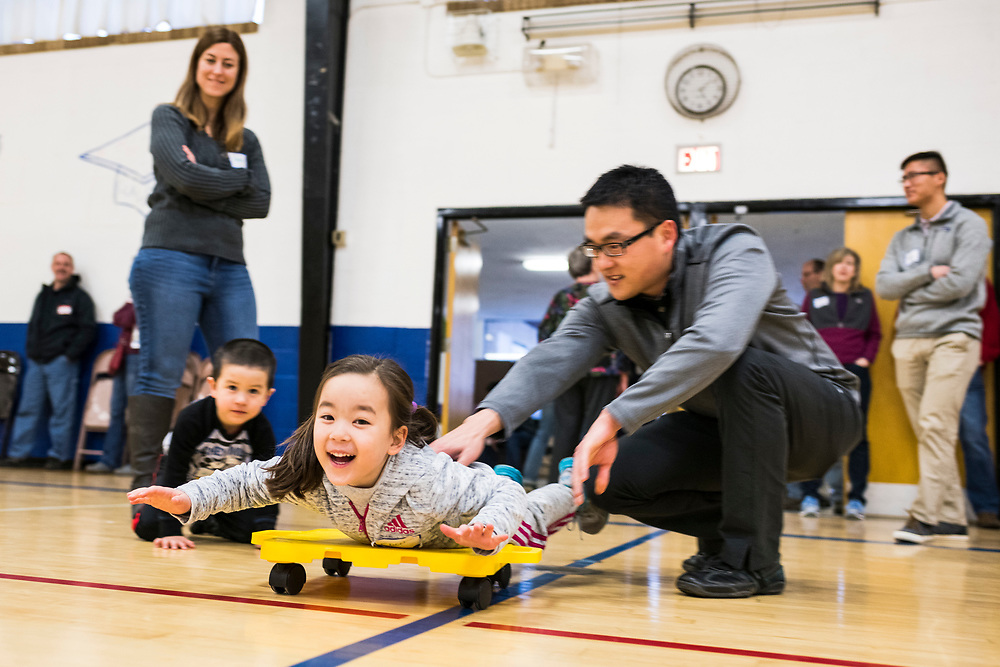New members Rachel and Adam Clausen play with their children, Zion and Eden, during a lunar new year event hosted by Families Through Korean Adoption (FTKA) in the gym and school cafeteria of St. Dennis Church in Madison, Wis., on Feb. 10, 2018. The event celebrated the passing of the lunar new year, and is one of several events for FTKA-member families and children to gather and enjoy cultural fun, food and play. (Photo by Jeff Miller - www.jeffmillerphotography.com)