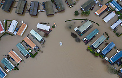 © Licensed to London News Pictures. 22/12/2019. Yalding, UK. A white inflatable dinghy makes it's way through flood water at The Little Venice caravan park near Yalding in Kent  after the nearby River Medway burst its banks. River levels remain high after a second night of heavy rain in the south. More rain is expected today. Photo credit: Peter Macdiarmid/LNP