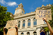 23 JULY 2020 - DES MOINES, IOWA:  Black Lives Matter protesters hold up signs calling for the release of Viet Tran at the Polk County Criminal Court Thursday. About 75 members of Des Moines Black Lives Matter protested in support of Viet Tran, one of their members who was arrested by Des Moines Police on July 1. He was arrested on charges of disseminating classified or confidential police information because during an interview with a local TV station, he held a memo from the Des Moines Police Department naming individuals police wanted to arrest on vandalism charges. He got the memo from another Black Lives Matter protester. During today's bond hearing the court ruled that Tran should be released and subjected to electronic monitoring before the weekend.       PHOTO BY JACK KURTZ