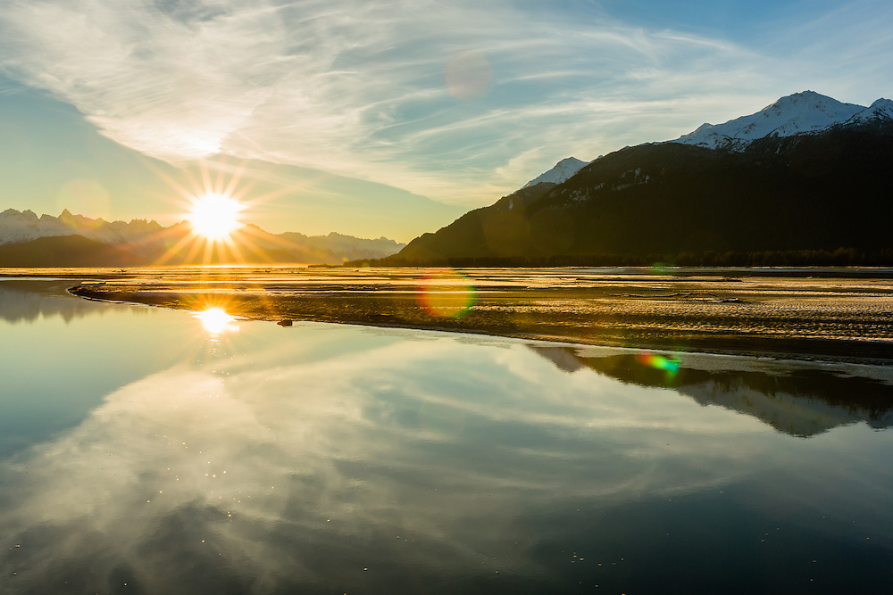 Sunrise over Haines mountains and reflection on the Chilkat River in the Chilkat Bald Eagle Preserve in Southeast Alaska. Winter. Morning.