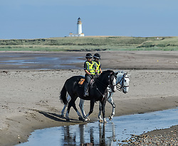 Pictured: Police, including mounted officers, were out in force around the hotel, including on Turnery beach, where they outnumbered protestors, with Turnery lighthouse in the background.<br /> <br /> Protesters gathered amid tight security at the Trump Turnberry resort, where President Trump and his wife Melania are staying on their trip to Scotland.<br /> <br /> &copy; Dave Johnston / EEm
