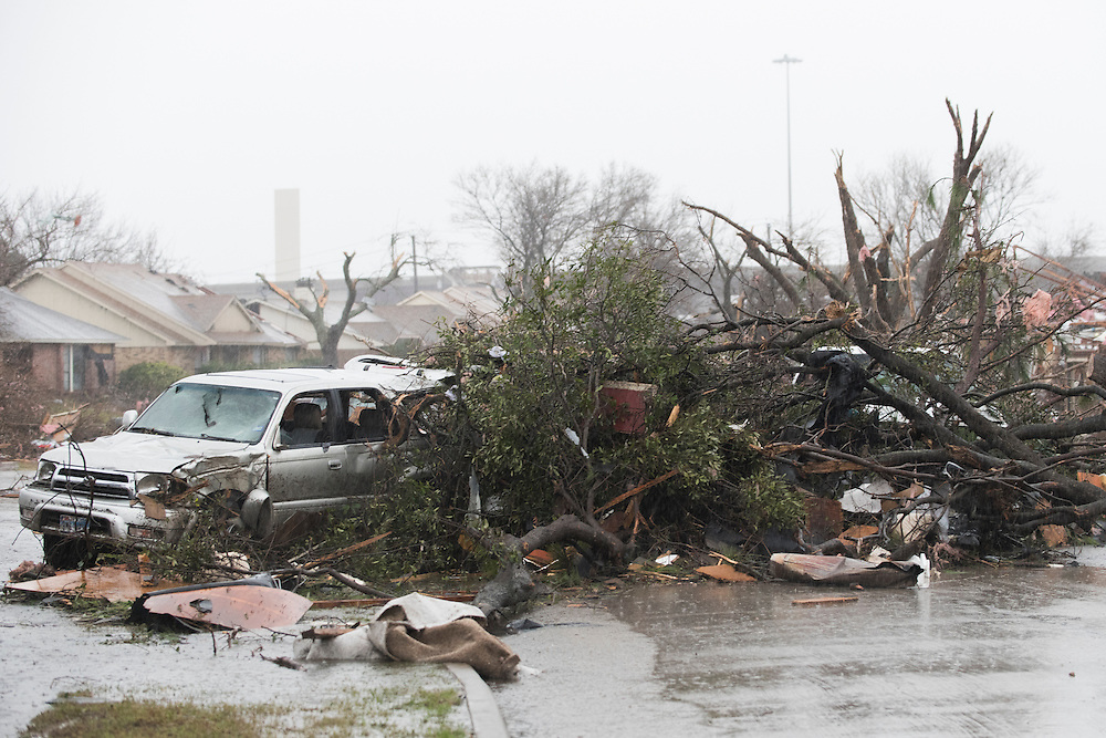 Debris is scattered around a neighborhood where homes were hit by a tornado the previous evening in Garland, Texas on December 27, 2015. (Cooper Neill for The New York Times)