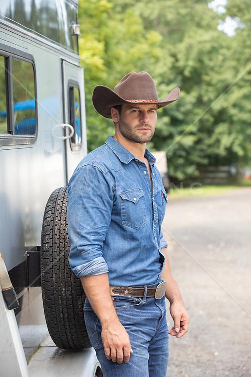 rugged cowboy by a trailer