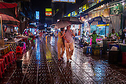 18 SEPTEMBER 2013 - BANGKOK, THAILAND:  Tourists walk down a rain slicked street in the rain looking for a restaurant in the Chinatown section of Bangkok. Thailand in general, and Bangkok in particular, has a vibrant tradition of street food and eating on the run. In recent years, Bangkok's street food has become something of an international landmark and is being written about in glossy travel magazines and in the pages of the New York Times.     PHOTO BY JACK KURTZ